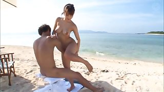 Intense cock-jerking action at the beach with an Asian doll